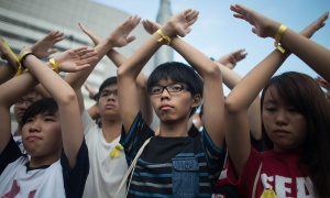 HONG KONG - OCTOBER 01:  Student pro-democracy group Scholarism convenor Joshua Wong (C) makes a gesture at the Flag Raising Ceremony at Golden Bauhinia Square on October 1, 2014 in Hong Kong. Thousands of pro democracy supporters continue to occupy the streets surrounding Hong Kong's Financial district. Protest leaders have set an October 1st deadline for their demands to be met and are calling  for open elections and the resignation of Hong Kong's Chief Executive Leung Chun-ying.  (Photo by Anthony Kwan/Getty Images)